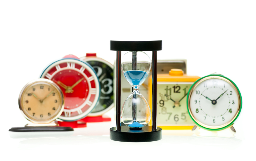 Sand timer with vintage mechanical wind-up alarm clocks on white background, shallow focus